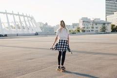 Hipster girl riding skate board Stock Image