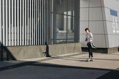 Hipster girl riding skate board Stock Images