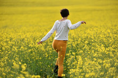 Hipster girl running through a canola field. Freedom concept Royalty Free Stock Image