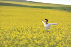 Hipster girl running through a canola field. Freedom concept Royalty Free Stock Photos