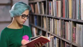 Hipster girl searching for book in a bookstore stock video footage