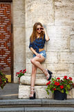 Hipster girl in shirt and denim shorts posing near the column. Stock Photography