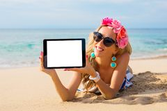 Hipster girl showing empty tablet on the beach, mockup for design. royalty free stock photography