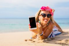 Hipster girl showing something on the phone while lying on the beach, mockup for screen design. Cheerful hipster girl showing something on the phone while lying Royalty Free Stock Photo