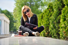 Hipster girl  shows tongue. Hipster girl with tablet in hand shows tongue Stock Photo