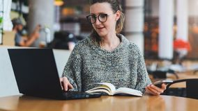 Hipster girl sits in cafe,uses smartphone,works on laptop.Businesswoman looks information message on computer screen. royalty free stock photography