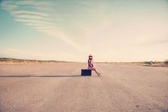 Hipster girl sits on suitcase. Happy hipster girl sits on vintage suitcase on road, space for text Stock Photography