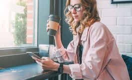 Hipster girl sitting in cafe at black table, drinking coffee and using smartphone. Businesswoman working online. Royalty Free Stock Photography