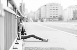 Hipster girl sitting on city street Royalty Free Stock Image
