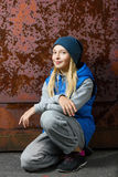 Hipster girl sitting on floor against red rusty Royalty Free Stock Photo