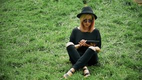 Girl Using Tablet. Hipster Girl Sitting On Green Grass In Park And Using Tablet. Slow Motion Effect stock video