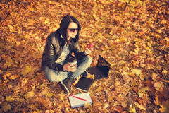 Hipster girl sitting on the leaves in the park Stock Photography
