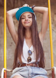 Hipster girl sitting on a swing Royalty Free Stock Photo