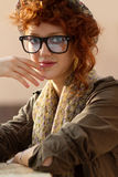 Hipster girl sitting at the table. Young hipster girl staring at your Royalty Free Stock Image