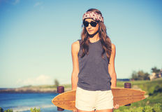 Hipster girl with skate board wearing sunglasses stock photo