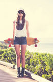 Hipster girl with skate board wearing sunglasses Royalty Free Stock Images