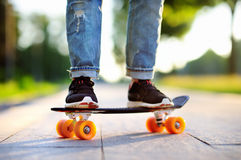 Hipster girl with skateboard outdoors. Closeup skateboarding royalty free stock photo