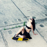 Hipster girl with skateboard. Young beautiful woman in sunglasses sitting on a skateboard on the concrete floor. Outdoors, lifestyle Royalty Free Stock Image