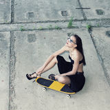 Hipster girl with skateboard. Young beautiful woman in sunglasses sitting on a skateboard on the concrete floor. Outdoors, lifestyle Royalty Free Stock Photos