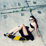 Hipster girl with skateboard. Young beautiful woman in sunglasses sitting on a skateboard on the concrete floor. Outdoors, lifestyle Stock Image