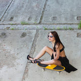 Hipster girl with skateboard. Young beautiful woman in sunglasses sitting on a skateboard on the concrete floor. Outdoors, lifestyle Stock Photos