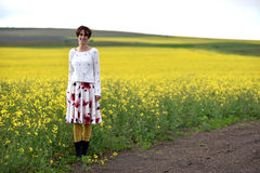 Hipster girl in skirt posing near a canola field Stock Photography