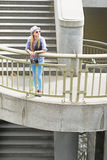 Hipster girl standing on stairs in city Stock Images