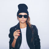 Hipster girl in sunglasses and black leather jacket smoking cigar Royalty Free Stock Photo