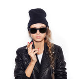 Hipster girl in sunglasses and black leather jacket smoking cigar Royalty Free Stock Photography