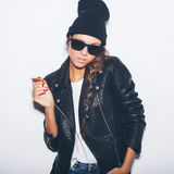 Hipster girl in sunglasses and black leather jacket smoking cigar Stock Images