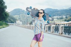 Hipster girl standing with longboard. Royalty Free Stock Image