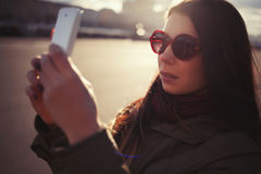 Hipster girl in sunglasses taking photo with smart phone Royalty Free Stock Images