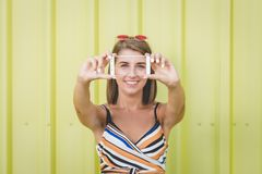 Hipster girl taking self portrait by using mobile phone against yellow wall. stock image