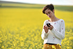 Hipster girl texting a message in the middle of a canola f Royalty Free Stock Image