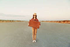 Hipster girl traveler. Smiling hipster girl traveler holds retro suitcase on road, space for text Stock Images