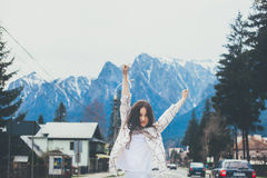 Hipster girl traveler wearing casual shirt. With arms raised on mountain background stock image