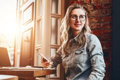 Hipster girl in trendy glasses sits in cafe at table in front of stock photo