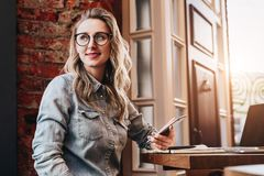 Hipster girl in trendy glasses sits in cafe at table in front of stock image