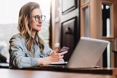 Hipster girl in trendy glasses sits in cafe at table in front of laptop, holding smartphone while looking out window. royalty free stock images