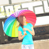 Hipster girl with umbrella. An ordinary girl with a rainbow umbrella on the roof of a house on a background of graffiti Royalty Free Stock Photography