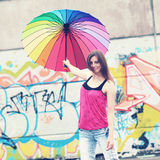 Hipster girl with umbrella. An ordinary girl with a rainbow umbrella on the roof of a house on a background of graffiti Stock Image