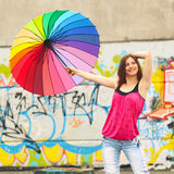 Hipster girl with umbrella. An ordinary girl with a rainbow umbrella on the roof of a house on a background of graffiti Stock Images