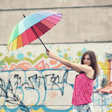 Hipster girl with umbrella. An ordinary girl with a rainbow umbrella on the roof of a house on a background of graffiti Stock Photo