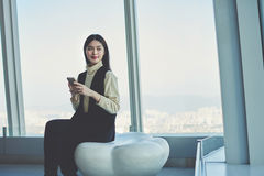 Hipster girl is using cell phone, while is sitting in modern loft indoors Stock Image