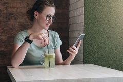 Hipster girl using digital gadget,working,blogging, chatting. Online marketing, education, social media, network. Young woman in glasses sitting in cafe at table Royalty Free Stock Photography