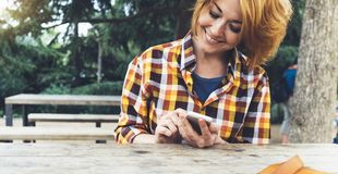 Hipster girl using phone technology internet, blogger person holding mobile smartphone on background sun city, female hands text. Ing online message on relax stock images