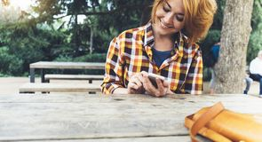 Hipster girl using phone technology internet, blogger person holding mobile smartphone on background sun city, female hands text stock photo
