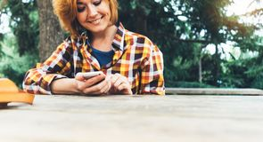 Hipster girl using phone technology internet, blogger person holding mobile smartphone on background sun city, female hands textin. G online message on relax royalty free stock image