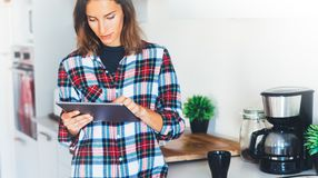 Hipster girl using tablet technology and drink coffee in kitchen, girl person holding computer on background interior cuisine, fem. Ale hands texting message on royalty free stock photo