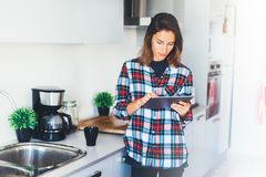 Hipster girl using tablet technology and drink coffee in kitchen, girl person holding computer on background interior cuisine, fem. Ale hands texting message on stock image